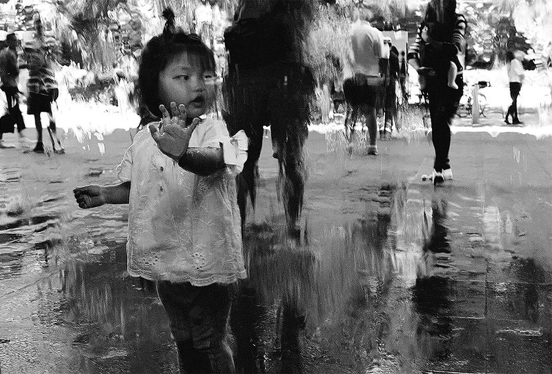 a child holds their hand against a glass window that has water running down it.