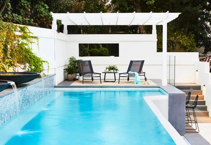 Pool with water feature, sitting area and pergola.