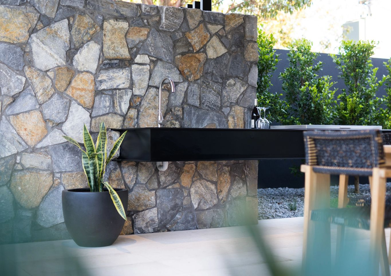 floating outdoor bench with sink and stone wall