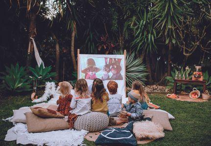 children watching a movie in the backyard