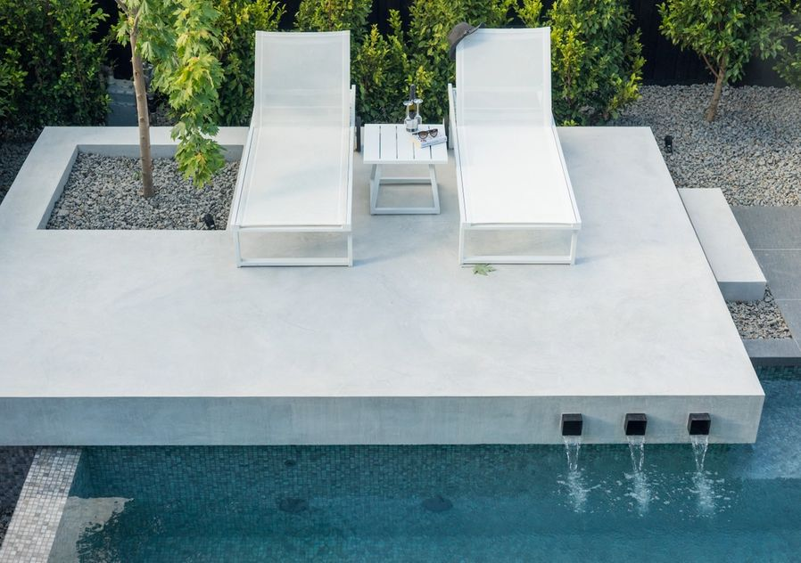 sun lounges next to pool with water feature