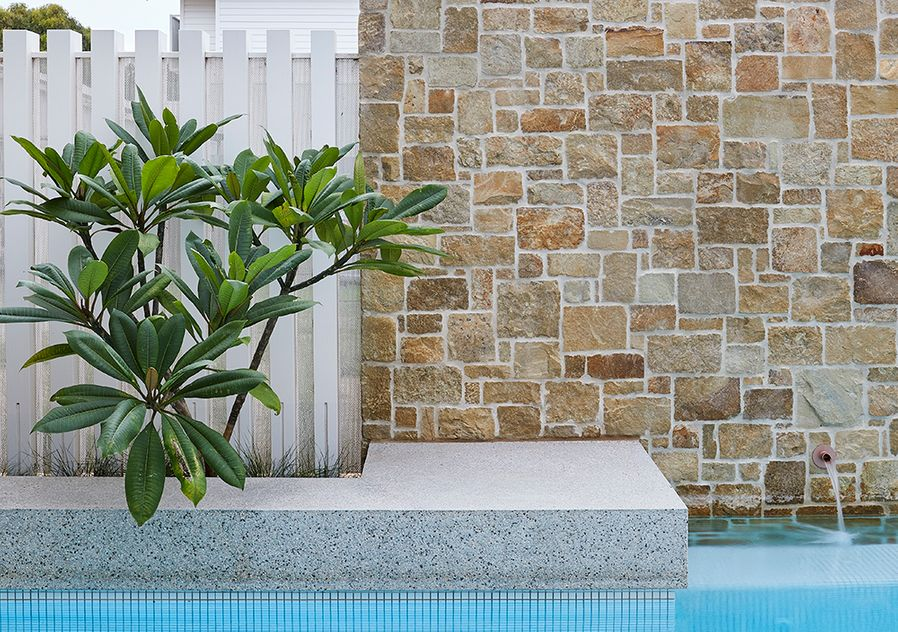 Pool tile feature photo with stone wall and green-blue spa tiles.