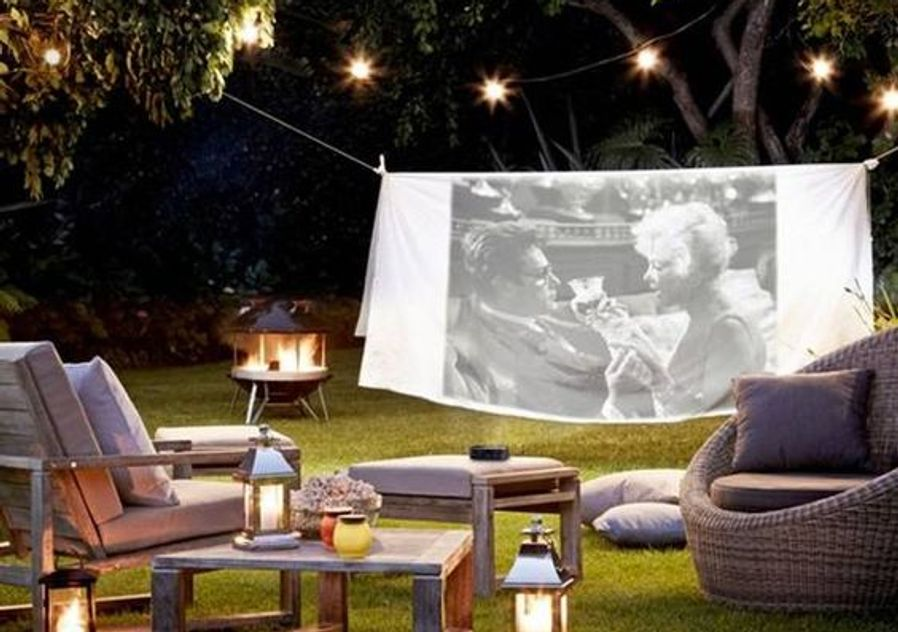Outdoor cinema screen at home with snacks and wine