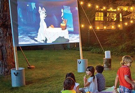 Kids watching lady and the tramp movie on a screen in the garden