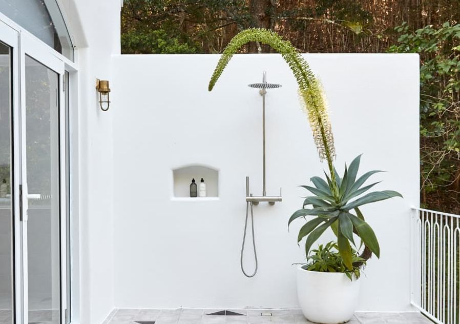 Outdoor shower against white wall