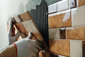 Kädet tekemässä kylpyhuoneen laatoitusta
