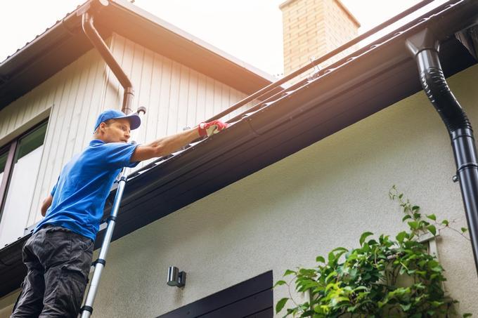 Mies puhdistaa kattoa.