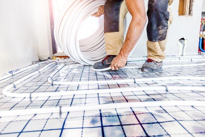 Mies asentaa vesikiertoisen lattialämmityksen putkia