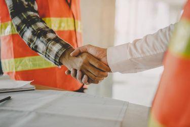 Kaksi henkilöä kättelevät rakennusluvan tiimoilta