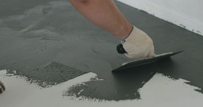 Urakoitsija levittämässä mikrosementtiä lattialle