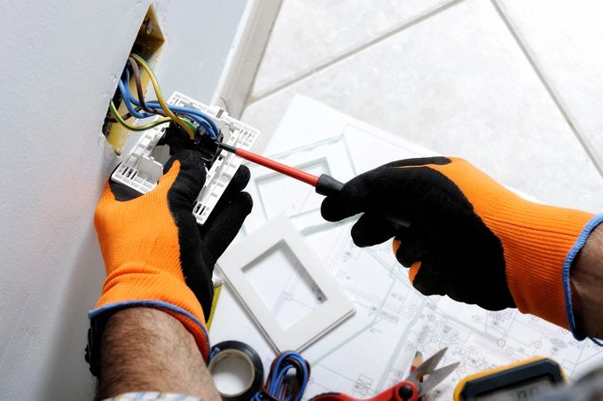Sähkömies tekemässä pistorasian sähköasennusta