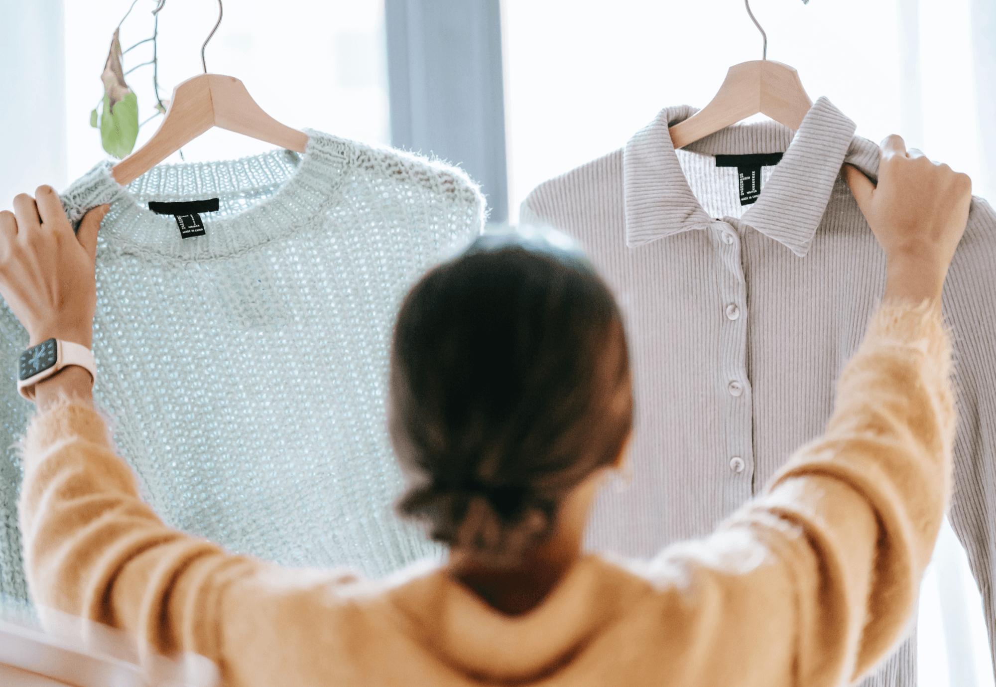 Frau wählt Kleidung aus.