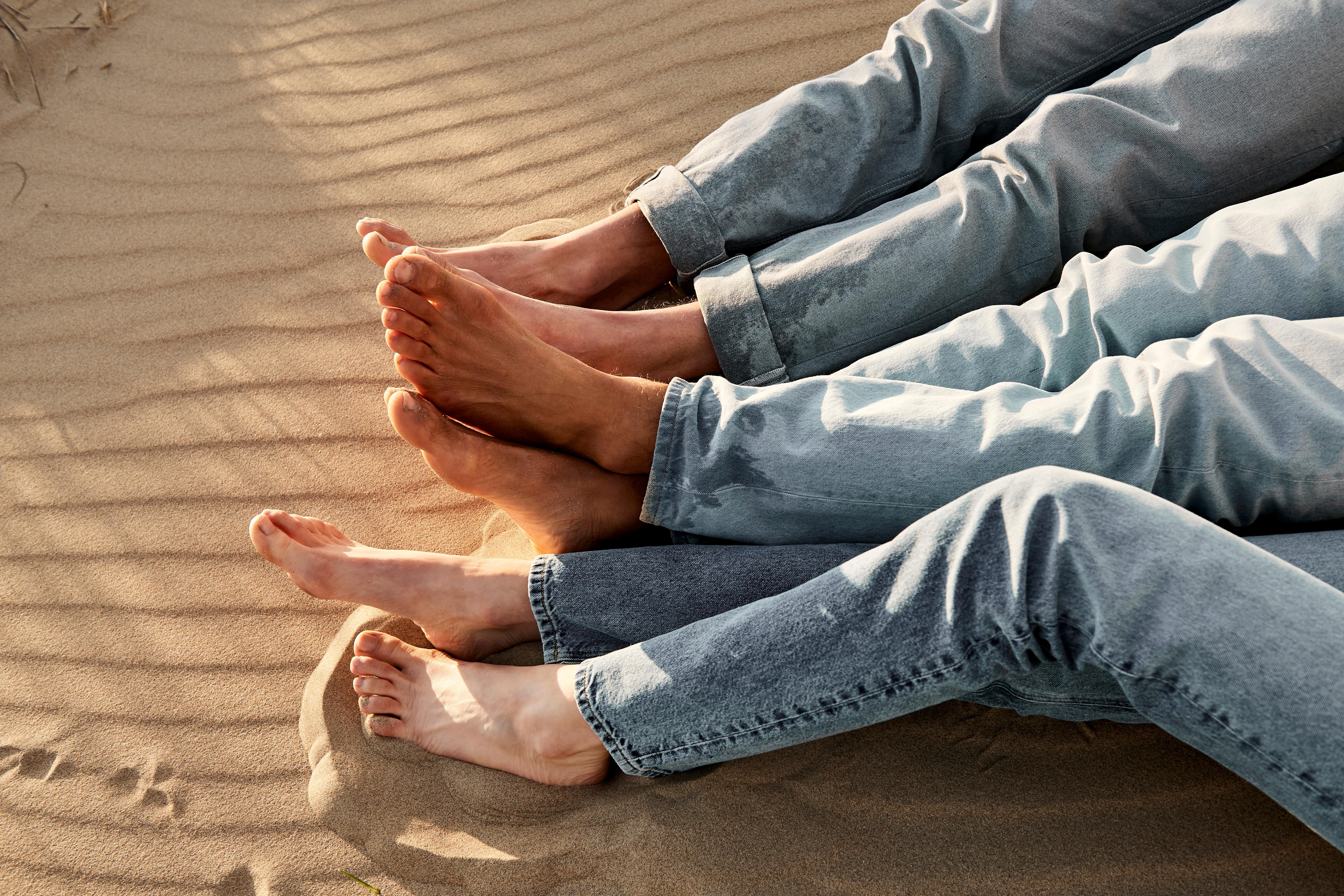 Menschen in Jeans sitzen im Sandstrand.