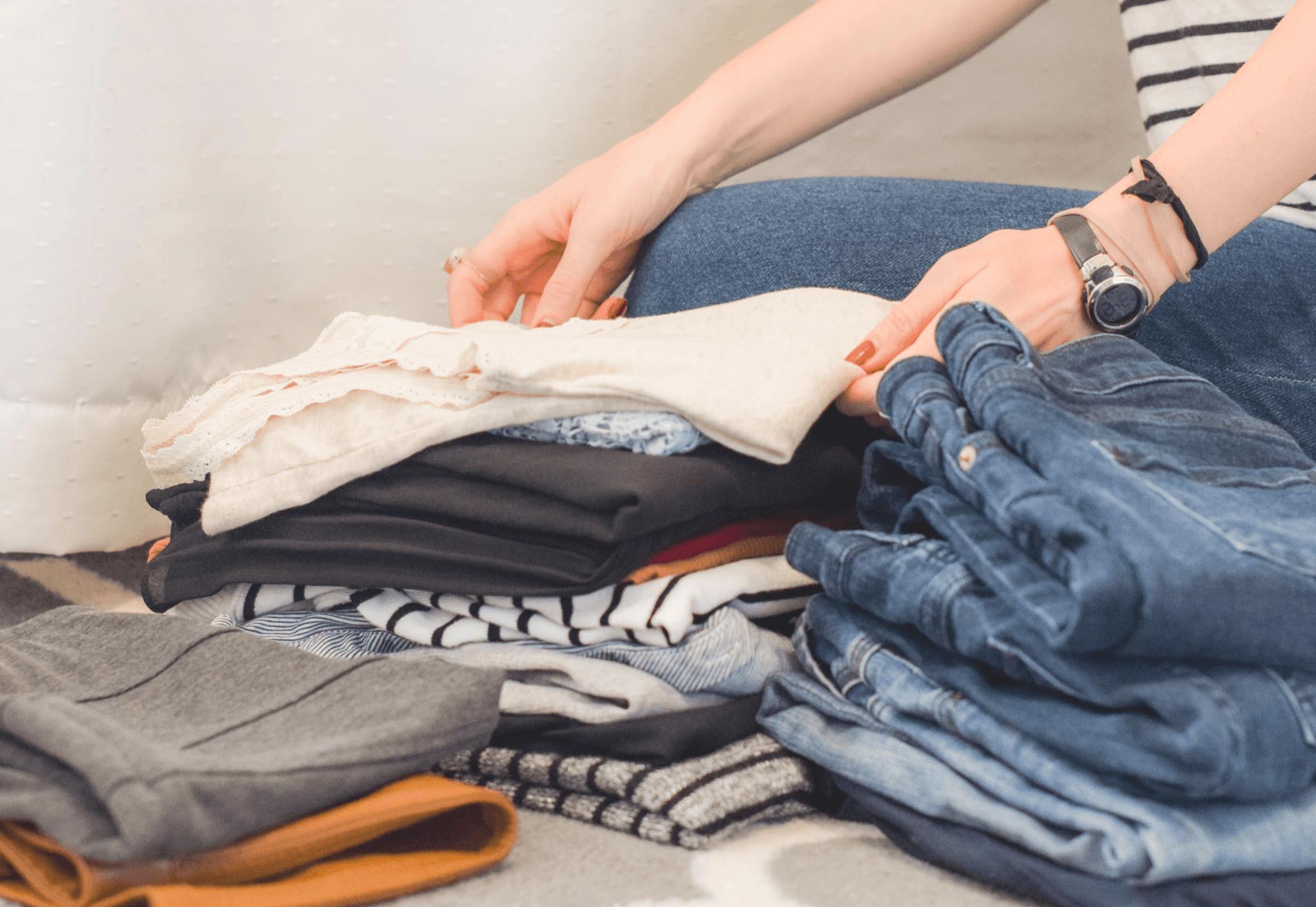 Frau legt Kleidung zusammen