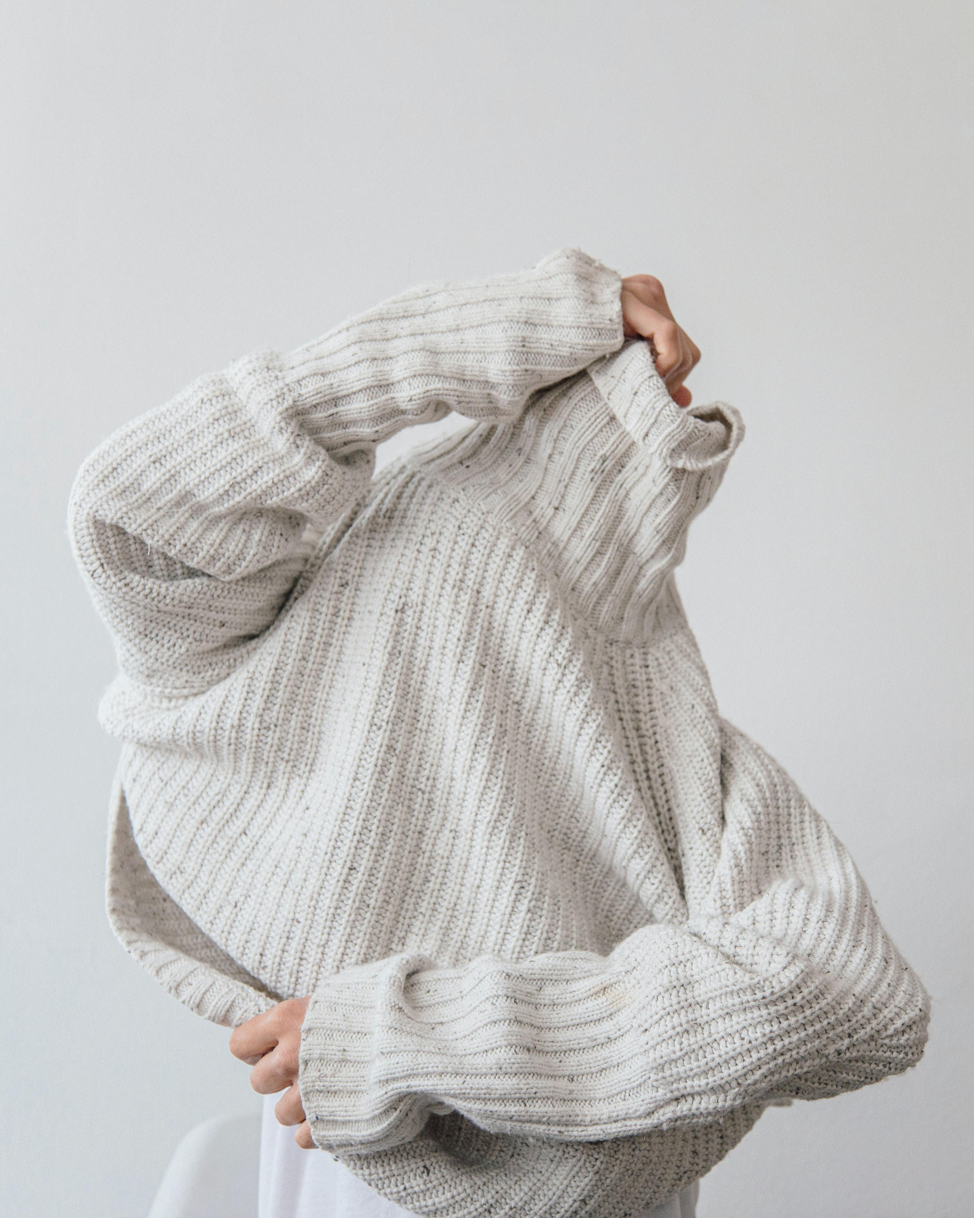 Pulling a sweater over.