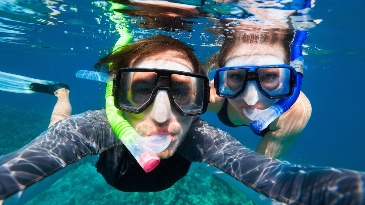 Adventurous couple goes snorkeling along the shores of Hawaii