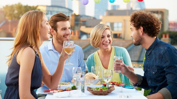 Friends enjoy a dinner while on a culinary trip.