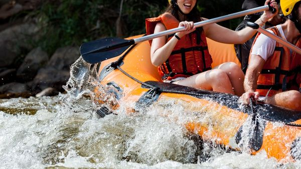Group of people rafting in white water rapids