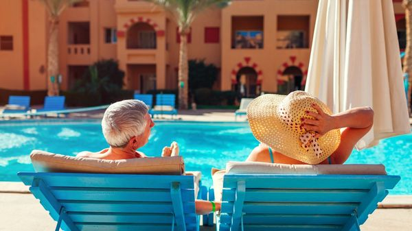 A couple enjoying a conversation beside the pool at an all inclusive resort near their home in California