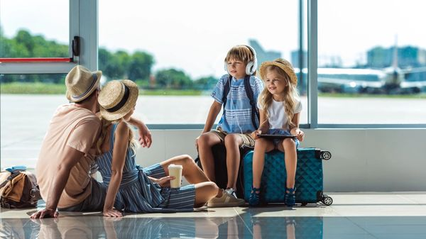 Family taking a break in the airport while traveling to their vacation destination