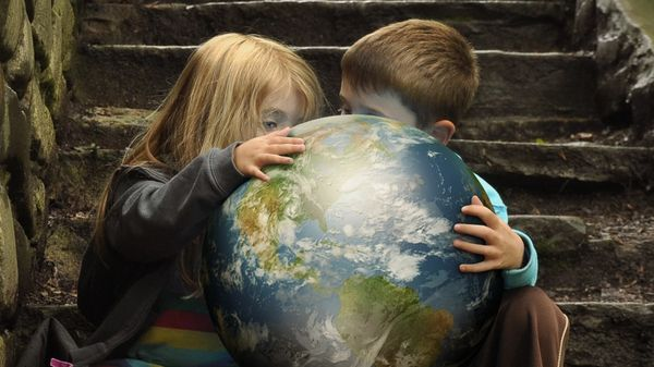 Two children studying a bright globe on a dark stairwell