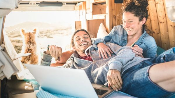 A hipster couple browse freelance jobs on their laptop from the back of their van
