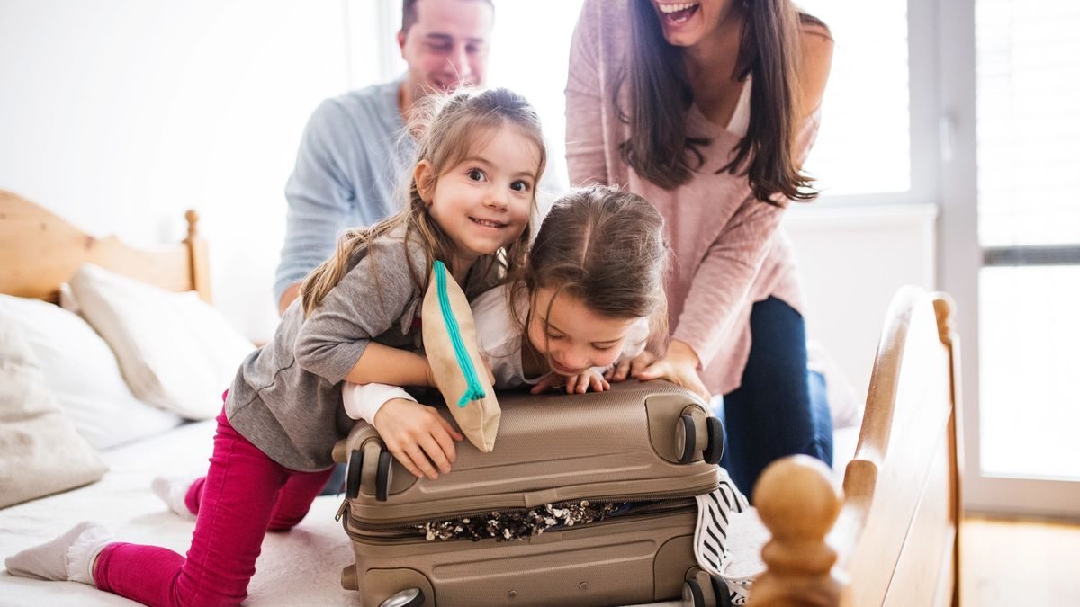 Mom and dad laugh while they pack a suitcase with two kids