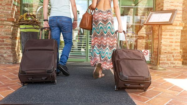 A couple arrives with their luggage for a relaxing all-inclusive vacation.
