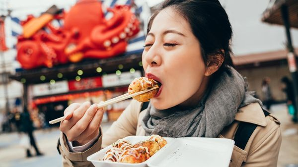A tourist eating delicious vegetarian tacoyaki balls