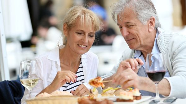 A senior couple sits down at an outdoor restaurant for healthy open air dining