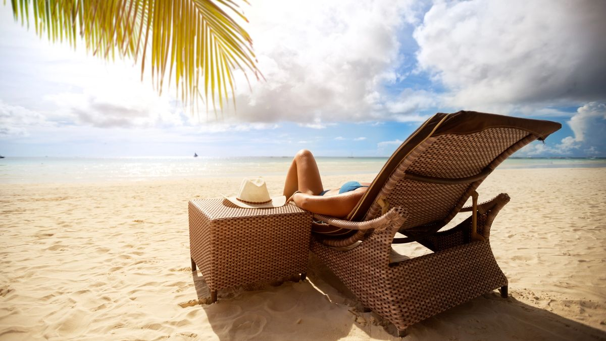 Woman on a luxury vacation in a leisurely beach-side chair.