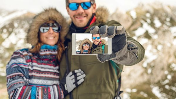 Couple takes a selfie outside in their winter coats while on vacation.