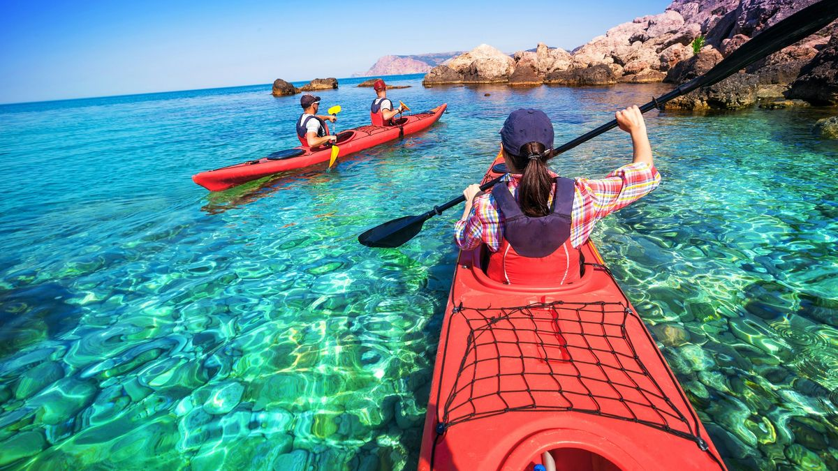 Friends meet at the kayak rental to pick up their boat and paddle in the sea