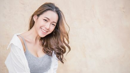 Asian woman in tank top and shirt with soft curls
