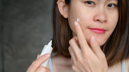 A woman applying a product to treat her skin