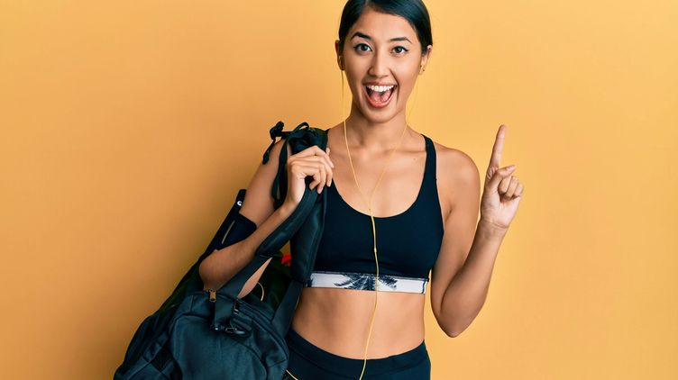 A beautiful Asian woman with a big smile holding a black gym bag