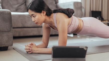 A woman in a pink fitness attire doing a plank
