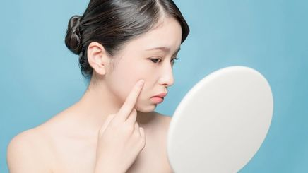 An Asian woman checking her face in the mirror