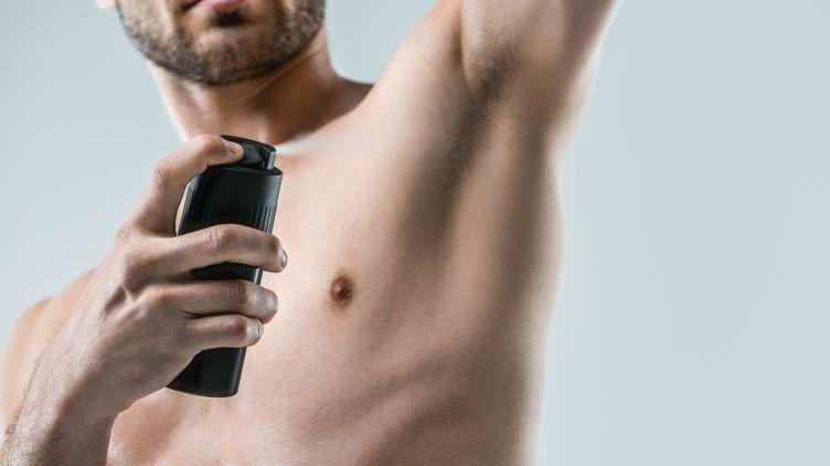 Man spraying deodorant on his body