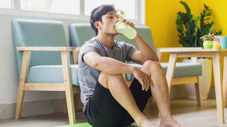Man drinking a bottle of water on the yoga mat.