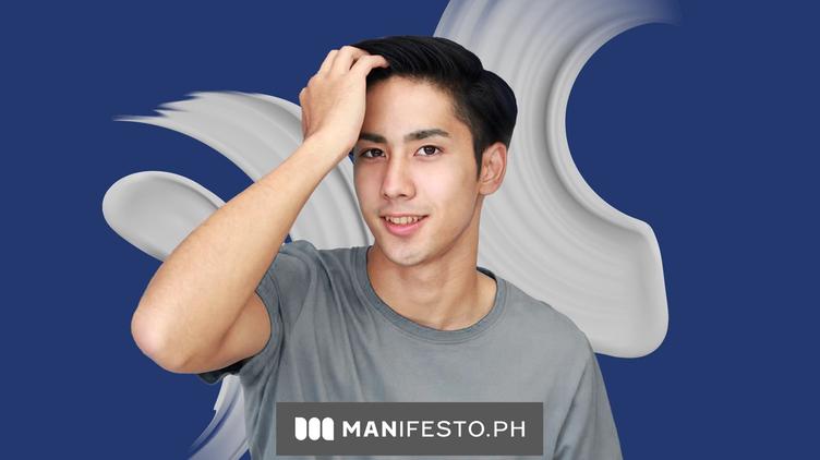 Asian man in gray shirt running fingers through hair