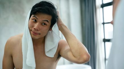 An Asian man rubbing a towel on his hair and looking at himself in the mirror