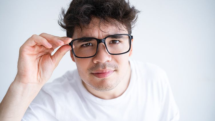 A man with curly hair and glasses in the front of whwall