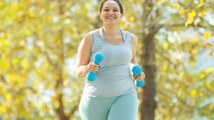 A plus-size woman jogging with hand weights
