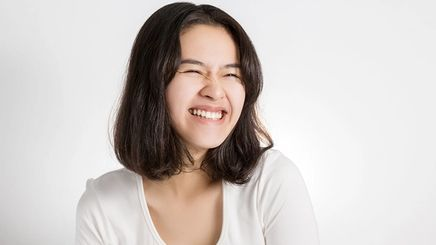 Asian woman with mid-length hair and a big smile