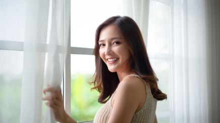 Beautiful Asian woman opening the window and smiling at the camera