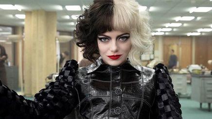 Emma Stone as Cruella wearing black and white wig