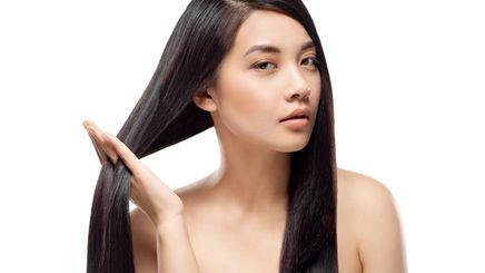 An Asian woman touching her long, healthy hair
