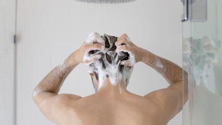 Young asian man washing his hair