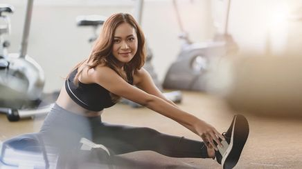 A beautiful Asian woman stretching at the gym